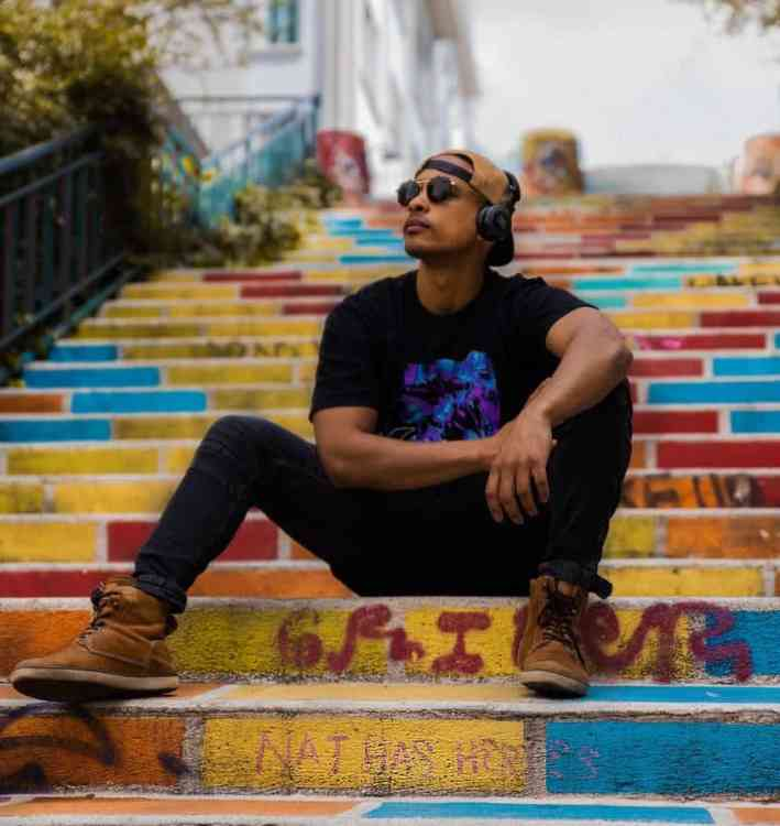 man listening to music with headphones on colorful steps