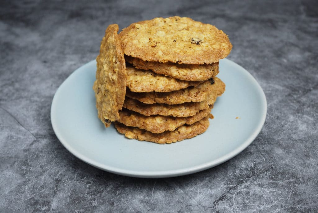 Stacks of thin-crispy oatmeal raisin cookies on a light grey plate on top of a cement working surfac.