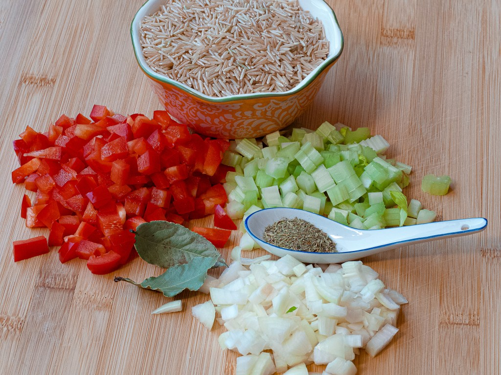Bowl of raw brown basmati rice, a spoon of dried thyme, 2 bayleaf and diced red bell pepper, celery and onion.