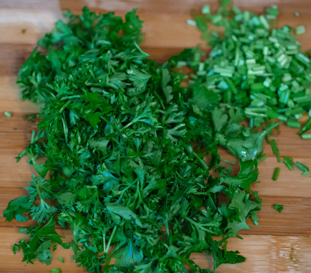 Parsley leaves and chopped parsley stems on the chopping board