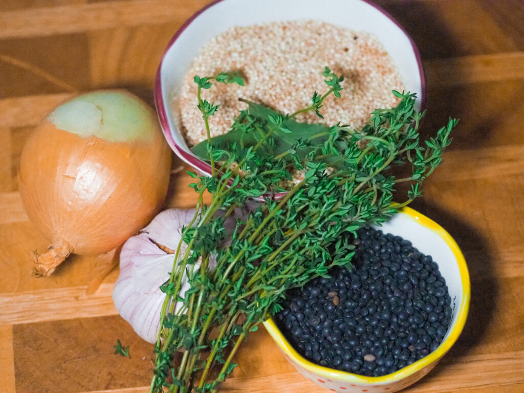 A cup of beluga lentils, bulb of garlic, sprigs or thyme, one cooking onion and a cup of quinoa on a chopping board