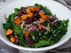 A bowl of chopped kale, roasted purple and orange sweet potatoes, thinly sliced red onion and sunflower seeds in a white serving bowl.