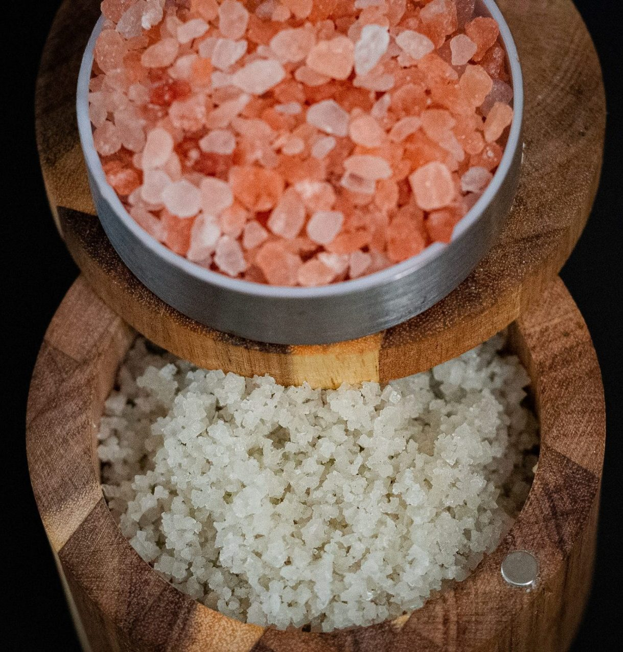 Pink himalayan and sea salt in a brown wooden salt container