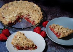 Sliced strawberry-rhubarb pie crisp with almond-oat streusel toppings on a dark grey patterned working space adorn with fresh strawberries.