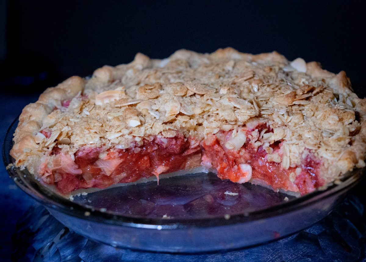 strawberry-rhubarb pie crisp with almond-oat streusel toppings on a dark grey patterned working space adorn with fresh strawberries.