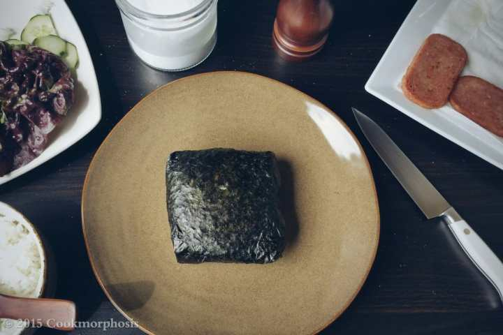 spam and egg onigirazu wrapped nicely in seaweed and placed on a large plate
