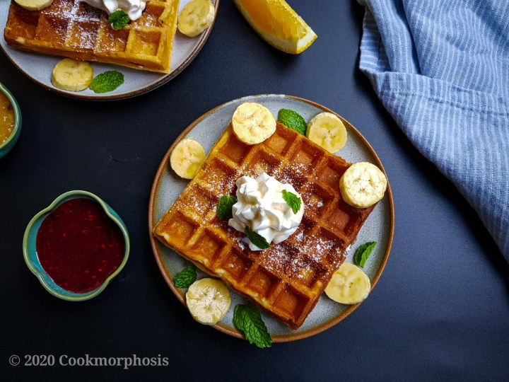 easy homemade waffles topped with banana, whipped cream and mint leaves