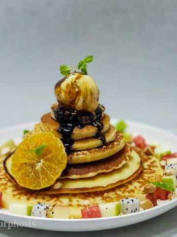 best homemade pancakes tower with fresh fruit, ice cream and syrup