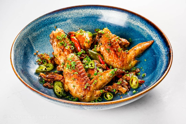 Fried confit chicken wings garnished with green onion, pickled jalapeno and thai chilies