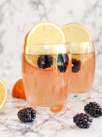 easy vodka mixed drink with slices of orange and black berries