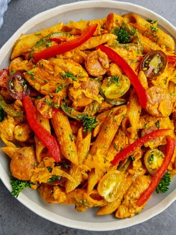 tasty and creamy cajun chicken pasta recipe topped with red bell pepper, parsley and cherry tomatoes