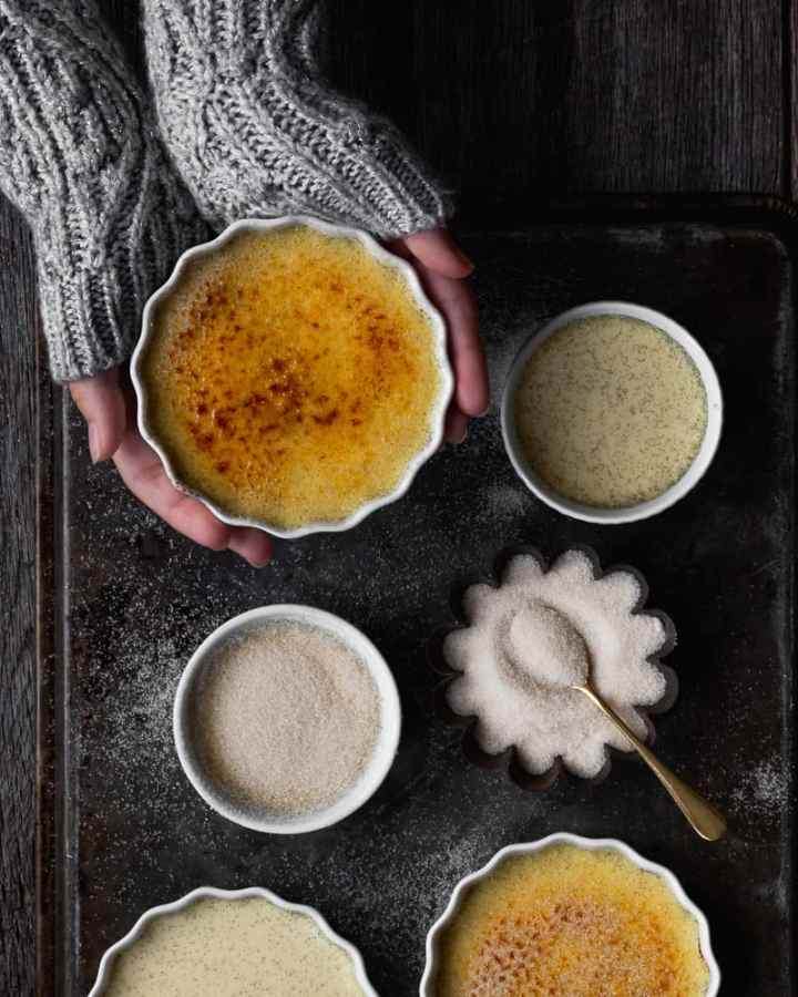 creme brulee on tray with sugar and hands holding one ramekin