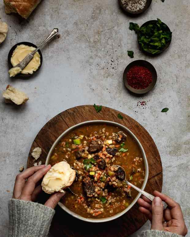 bowl of beef and barley soup with hands in frame
