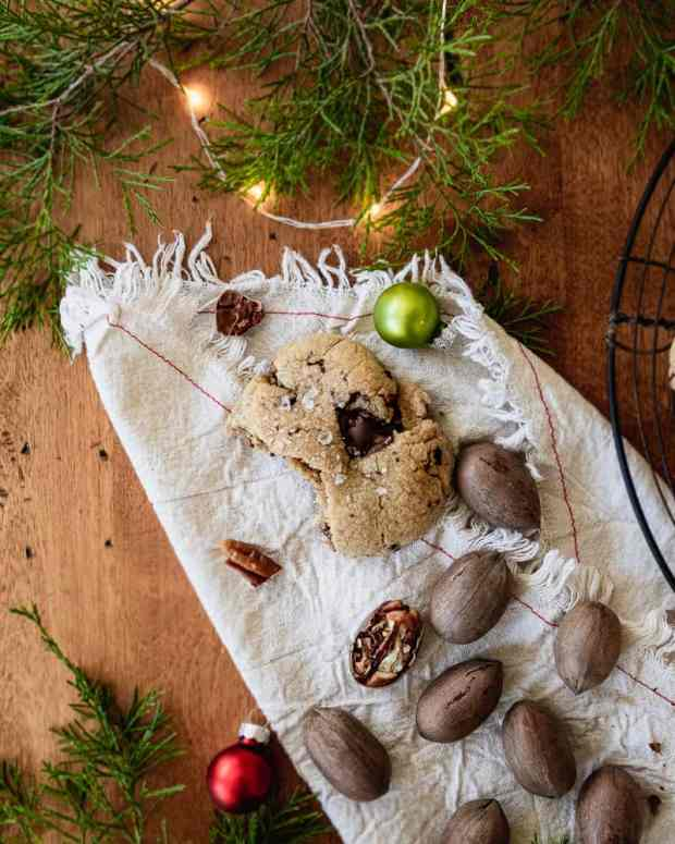 cookie on cloth napkin with pecans and holiday decorations
