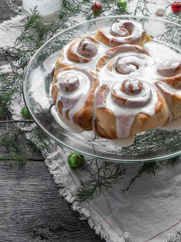 eggnog sweet rolls on cake stand with holiday greenery and decor