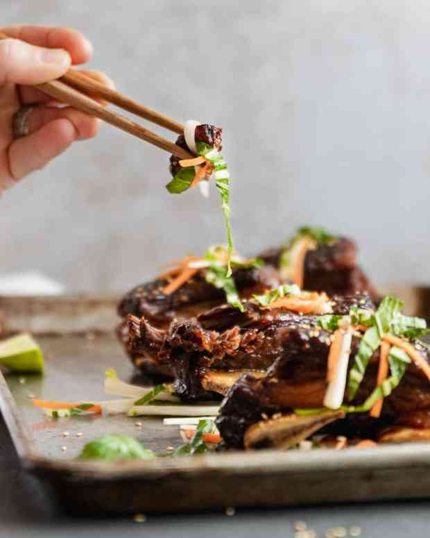 hand holding chop sticks with asian beef short ribs and slaw