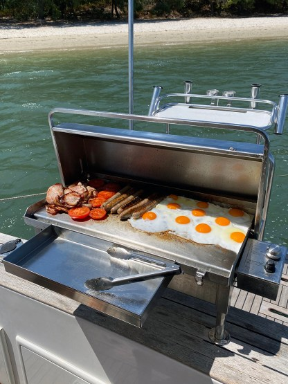 Stainless BBQ Accessory Utensil Tray with Deluxe Gas Boat BBQ on the back of a Riviera