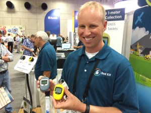 Brett Hackleman (founder and CTO) at their Bad Elf booth at the ESRI User's Conference in San Diego in July of 2015 holding their two featured Bluetooth GPS units.