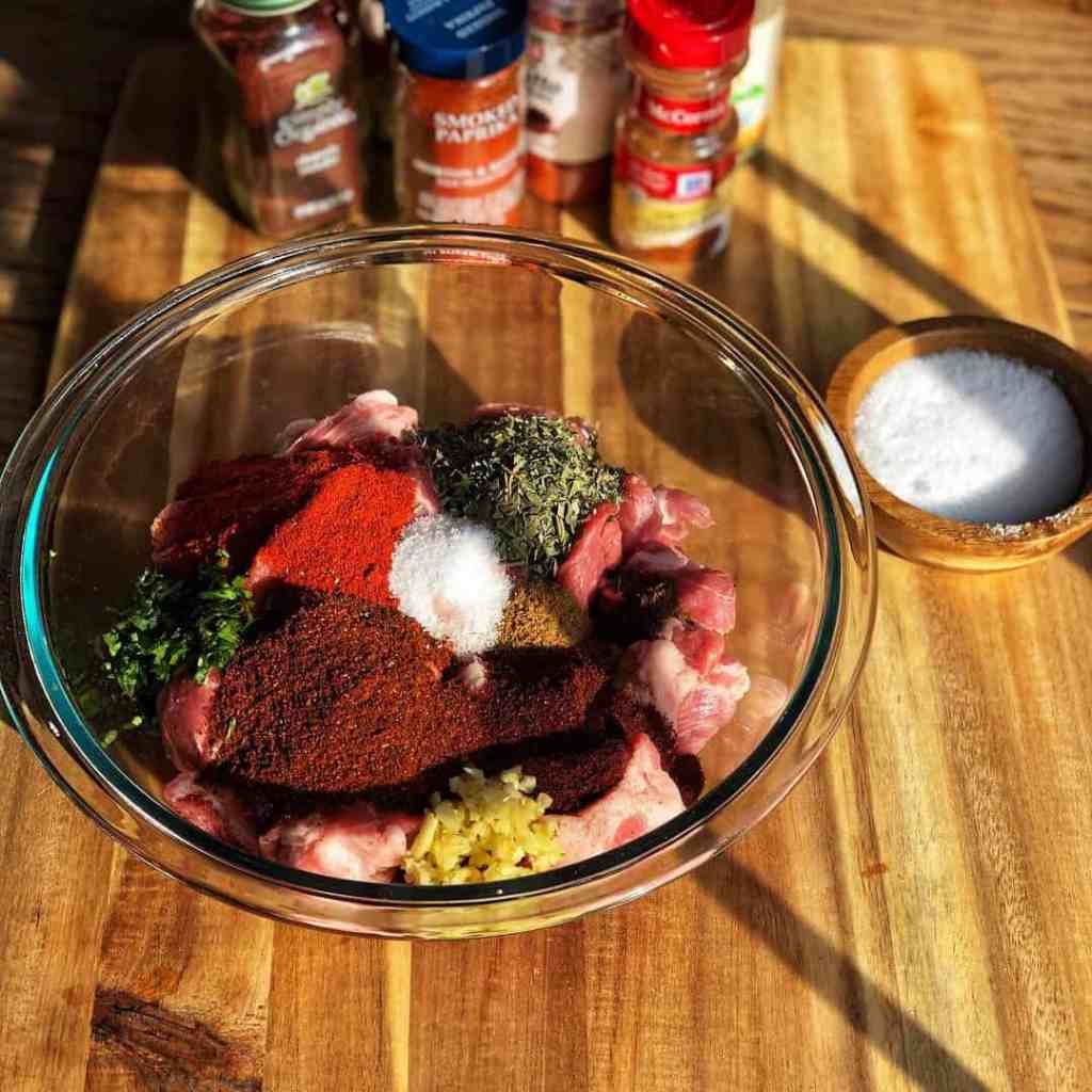 A glass bowl filled with ground pork and a variety of spices, for making homemade chorizo.
