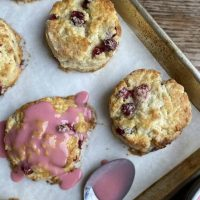 Sheet pan with cranberry orange scones and a spoon that has drizzled blood orange glaze over one of the scones.
