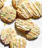 A pile of sprinkle sugar cookies with vanilla icing.