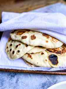 Garlic Butter Naan covered in a towel to keep warm.
