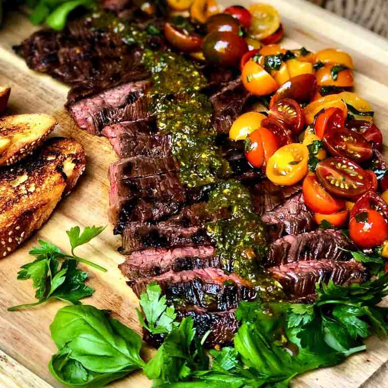 A wooden cutting board with toasted bread and Skirt Steak with Italian Chimichurri and Tomato Salad