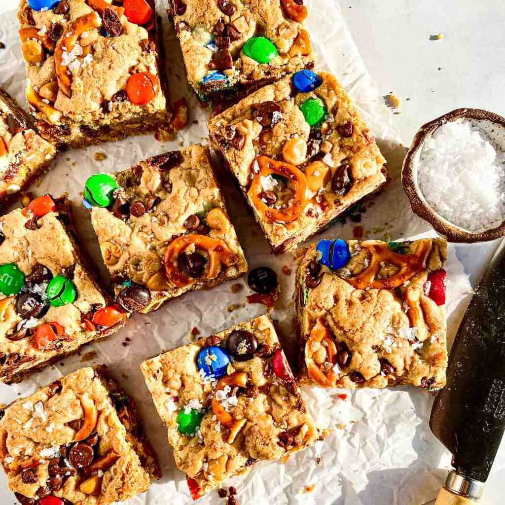 Brown Butter Blondies with M&Ms, pretzels, chocolate and peanut butter chips with a knife and flaky salt beside them.
