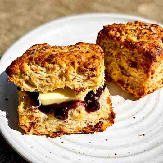 Bacon and Gruyere Biscuits, one of which has blueberry jam and butter.