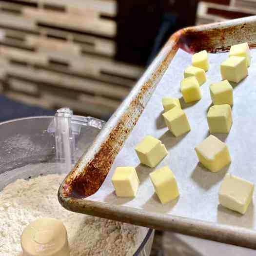 A sheet tray with cubes of frozen butter.