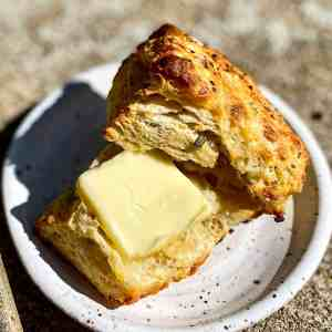 A buttered Rosemary and Romano Biscuit with Black pepper on a small white plate.