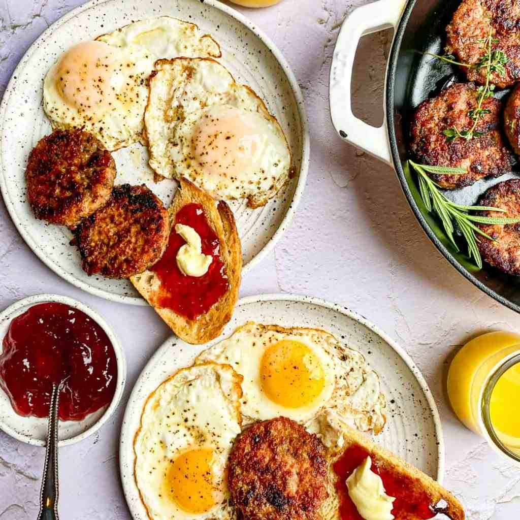 Eggs and toast on small white plates with patties of ground breakfast sausage.