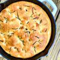 White cast iron pan containing No-Knead Rosemary-Garlic Focaccia Bread