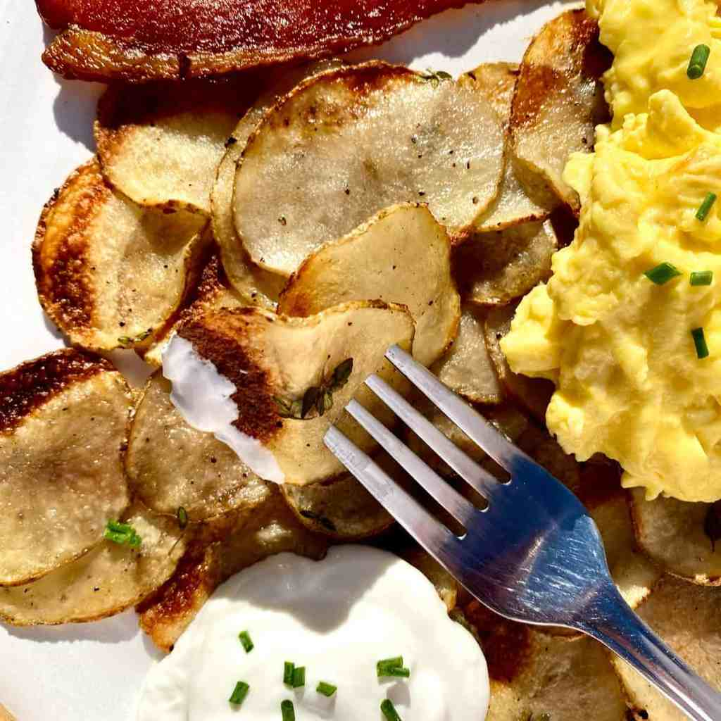 Crispy sheet pan potatoes with chive sour cream, scrambled eggs, and bacon on a white plate.
