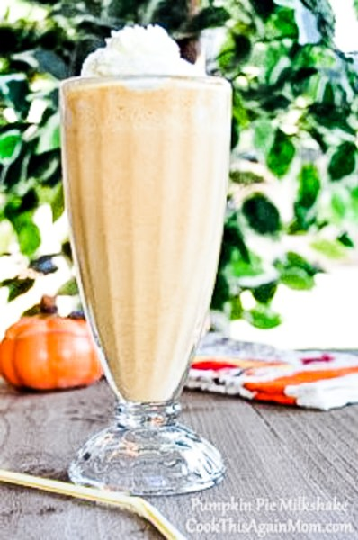 pumpkin milkshake topped with whipped cream in a tall glass