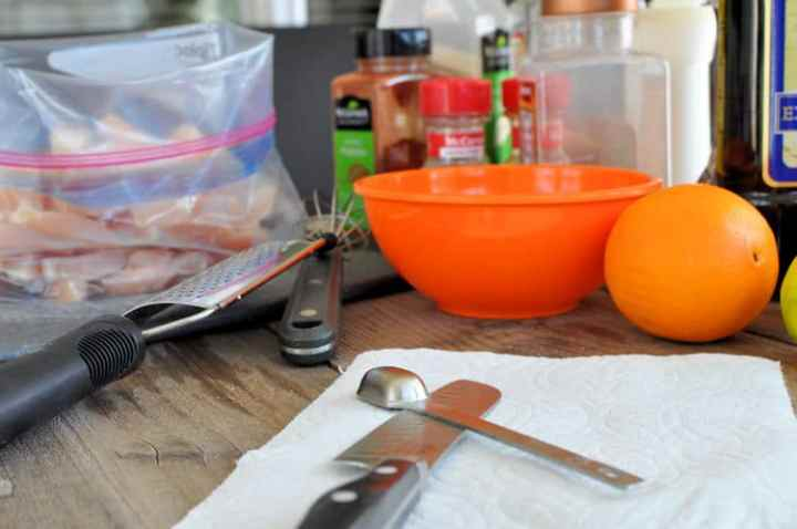 an orange, spices, a bowl, and utensils for prepping to prepare a citrus marinade for chicken fajitas