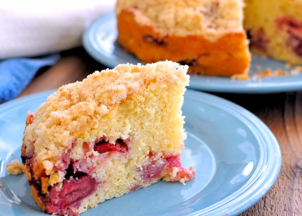 A slice of fresh strawberry coffee cake on a blue plate