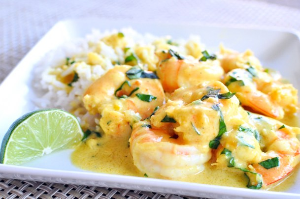 shrimp in a curry sauce with rice on a white square plate
