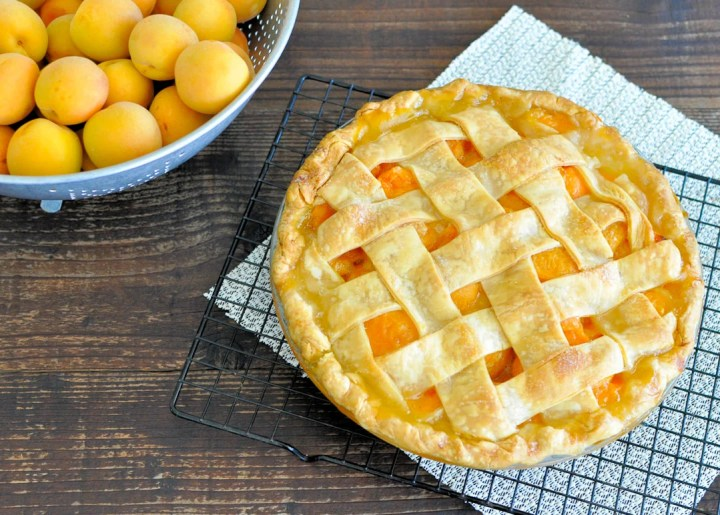 a fresh baked pie sitting next to a bowl of fresh apricots