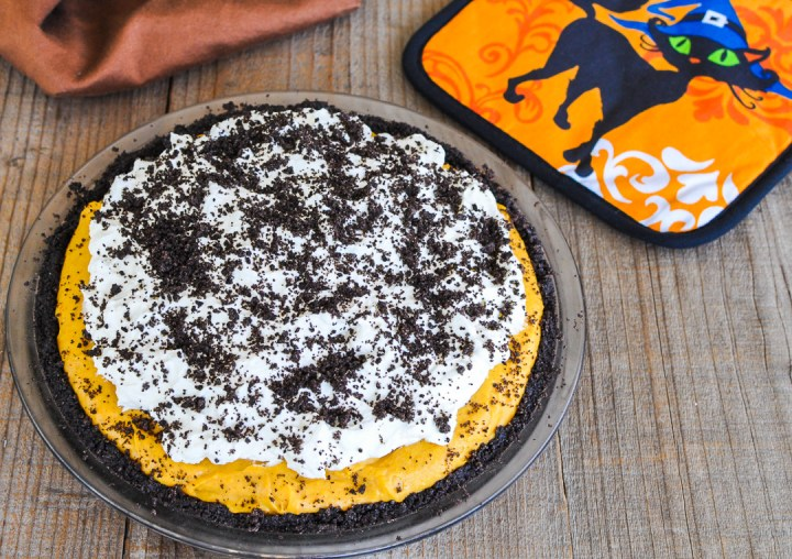 no-bake cheesecake, pumpkin and spice flavor, sitting on a wood backdrop next to a halloween kitty pot holder