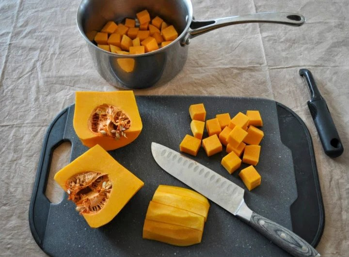 a butternut squash that has been peeled and is in the process of being cubed.