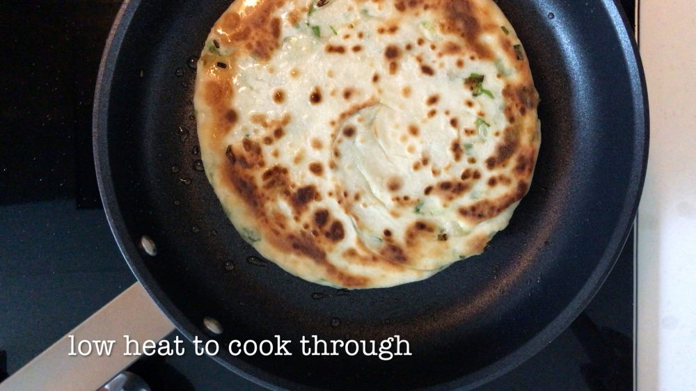 A golden brown scallion pancake is being cooked in a pan