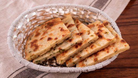 quartered savoury scallion pancakes in a silver basket