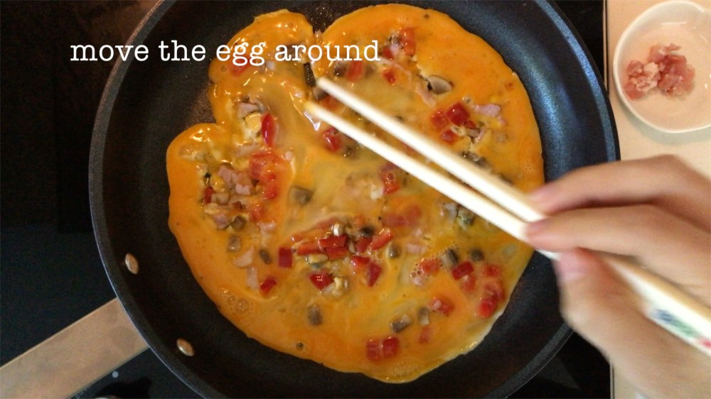 gently moving the egg mixture around to mix with the bacon, shallot, mushroom and red bell pepper