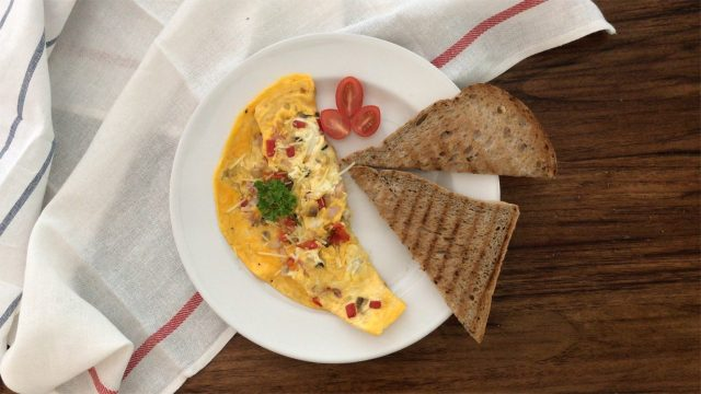 Serving the omelette with cherry tomatoes and brown toast