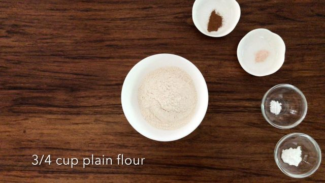 3/4 cup plain flour, 1 teaspoon baking powder, 1/2 teaspoon bicarbonate soda, 1/4 teaspoon of salt1/2 teaspoon ground cinnamon are in bowls and placing on a wooden table