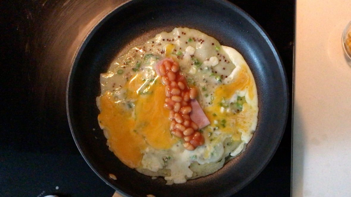 Some baked beans on a strip of ham on a cooking pancake