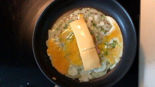 Two strips of Cheddar cheese on top of a cooking pancake