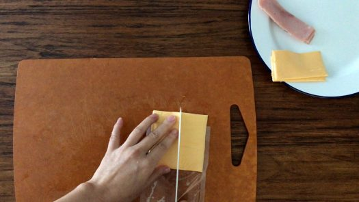 Cutting a piece of sliced Cheddar cheese