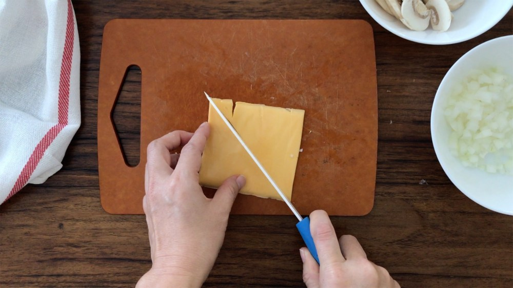 Cutting a slice of Cheddar cheese diagonally